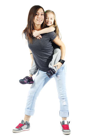 Mother giving her daughter a piggyback ride against white background photo