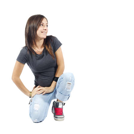 woman kneeling: Woman kneeling down looking to her left on white background Stock Photo