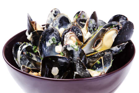 Bowl of mussels with cream sauce on white table cloth