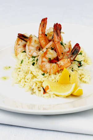 Shrimps on a bed of rice with lemon photo