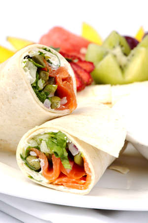 Smoked salmon wrap with assorted fruits on plate photo