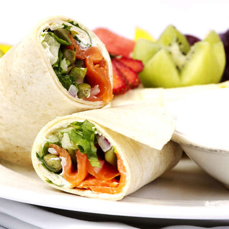 Smoked salmon wrap with assorted fruits on plate