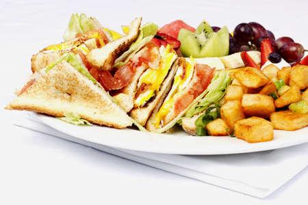papas doradas: Desayuno sándwich club y una variedad de frutas en un plato blanco