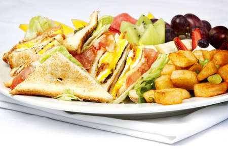 Breakfast club sandwich and assorted fruits on white plate photo