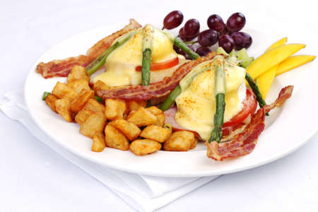 hashbrowns: Asparagus ham tomato eggs benedict with fresh fruit and hashbrowns Stock Photo