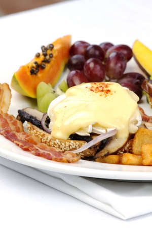 Portobello mushroom brie eggs benedict with bacon and fruits on side Stock Photo - 10542553