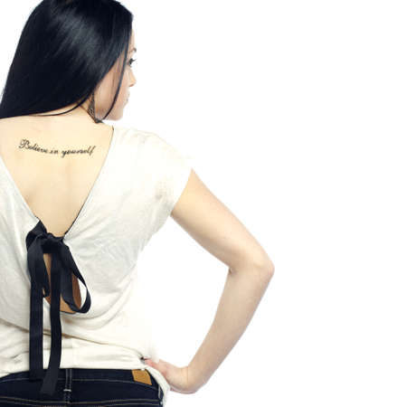 Young girl with back turned showing tattoo dressed for summer photo