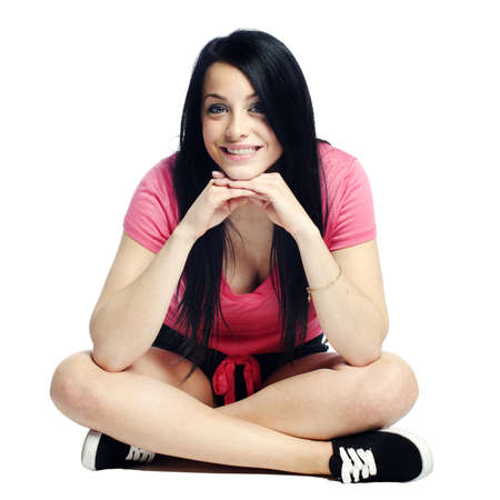 Happy and confident young woman sitting cross legged smiling with hands on chin