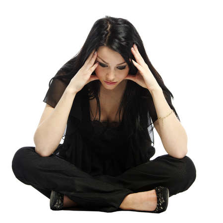 wonders: Young business casual woman worried with hands on head sitting