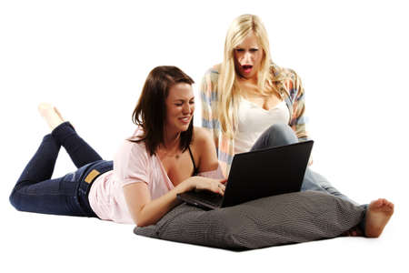 indoors: Pretty young girls shocked while watching a video on laptop - Isolated indoors Stock Photo