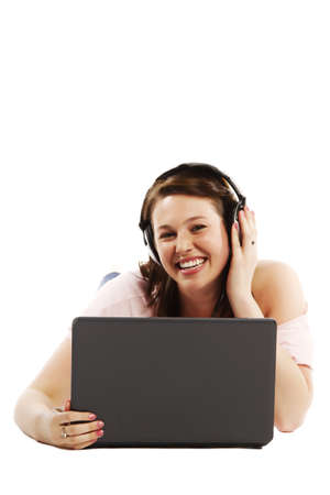 Happy young woman lying on floor listening to music on her laptop over white background  photo