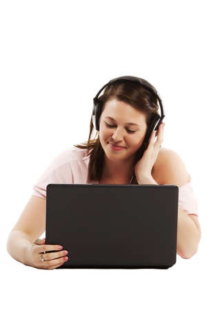 Casual pretty female listening to music on her laptop isolated over a white background  photo