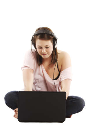 Young attractive woman wearing headphones sitting on the floor with a laptop photo
