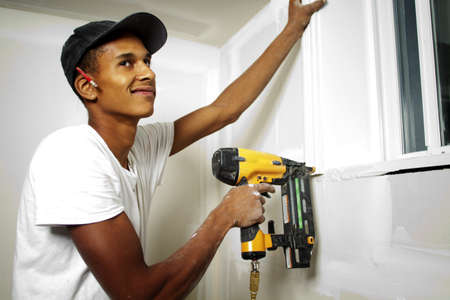 Portrait of a man drilling into a wall during renovations photo