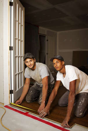 Multi ethnic team working on flooring in basement photo