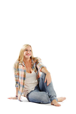 vertical composition: Full length image of attractive young female relaxing against white background - Vertical composition