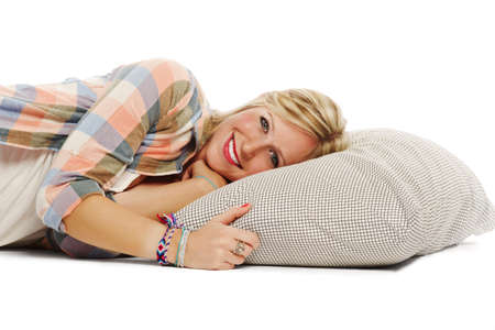 Portrait of attractive young female relaxing on pillow smiling at camera on white background Stock Photo - 12833102
