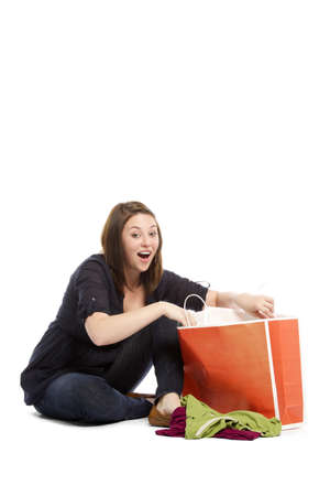 Portrait of young woman searching for her gifts in the bag sitting on white background photo