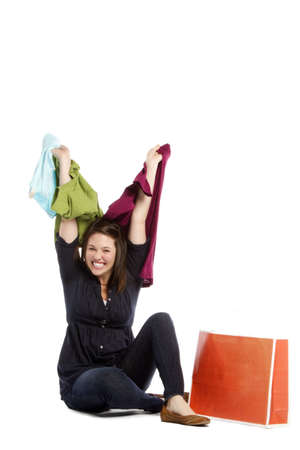 Shopaholic - Excited young woman with lots of clothes sitting on white background  Stock Photo - 12832394