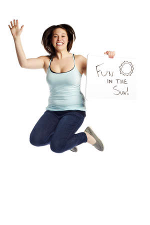 Happy young female jumping over white background holding a signboard - Fun in the Sun  Stock Photo - 12831731