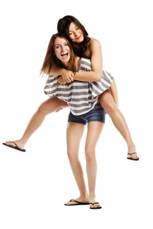 Friendly cute young female giving piggyback ride to a friend on white  photo
