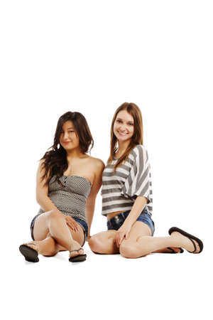 Young female friends relaxing on white background - vertical composition photo