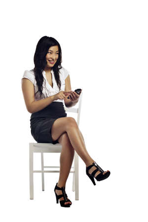 woman on phone: Asian business woman reading a message on her cell phone sitting against white background Stock Photo