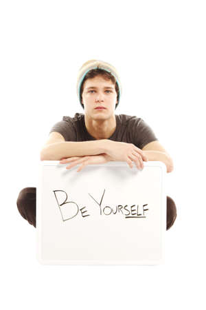 yourself: Young man dressed in hip style holding sign that says be yourself