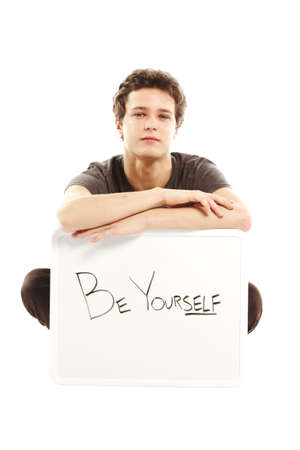 yourself: Young man dressed with hip style holding sign that says be yourself