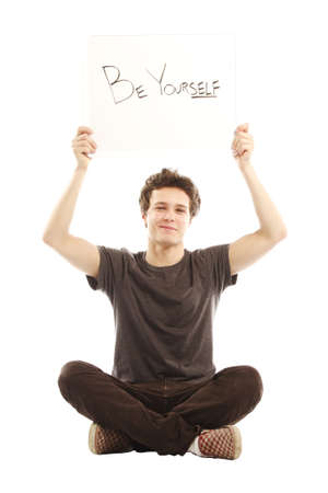 Young smiling man holding sign up saying Be yourself Stock Photo