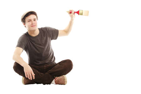 cool guy: Young smiling man holding paint brush against white background