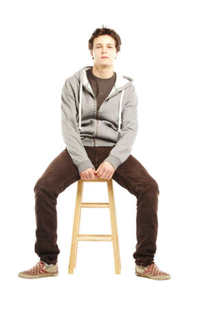 stool: Young man with hip style sitting on stool against white background