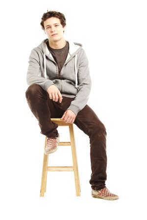 stool: Young handsome man with hip style sitting on stool against white background