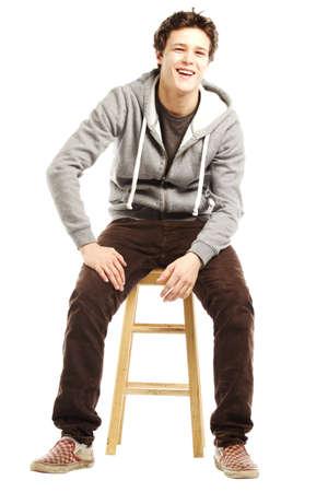 Jonge knappe man met hippe stijl zittend op kruk tegen een witte achtergrond Stockfoto