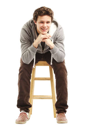 leaning forward: Young handsome man in hoodie sitting on stool leaning forward