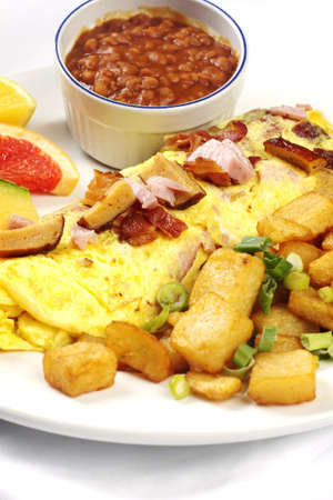 Meatlover omelet with beans and potatoes against white background