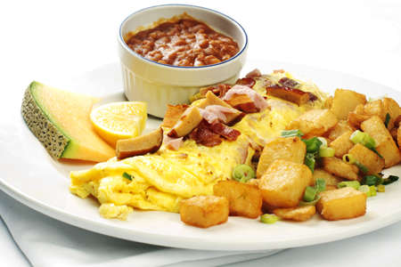Meatlover omelet with beans and potatoes against white background photo