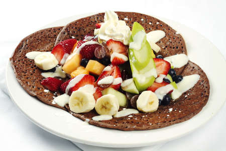 crepe: Three chocolate crepes with assorted fruits on top