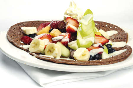 Three chocolate crepes with assorted fruits on top photo
