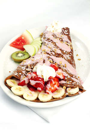 Chocolate crepe with banana strawberry topped and rasberry yogurt cereal topping photo