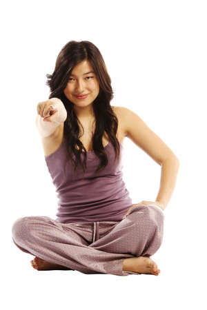 Young asian woman cross legged pointing at camera photo
