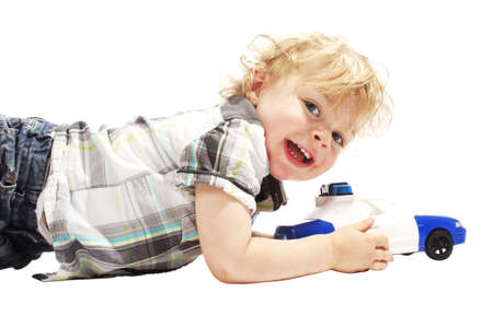 Cute little boy smiling and playing with police car against white background Stock Photo - 15217832