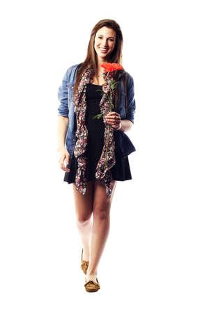 stepping: Teenage girl holding flower stepping forward smiling