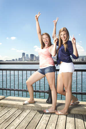 Two girls posing on city scape having fun photo