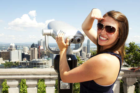 canada day: Beautiful girl standing by binoculars at tourist area with blue sky behind