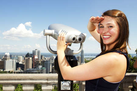 Beautiful girl standing by binoculars at tourist area with blue sky behind