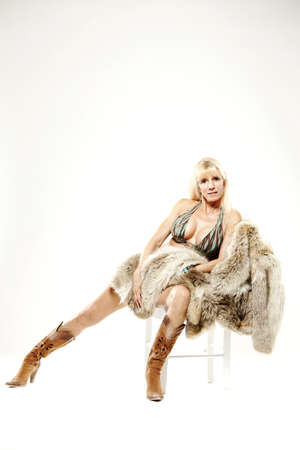 maturity: Mature woman in bikini and cowboy boots with fur