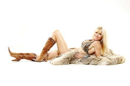 Rijpe vrouw in bikini en cowboy laarzen met bont Stockfoto