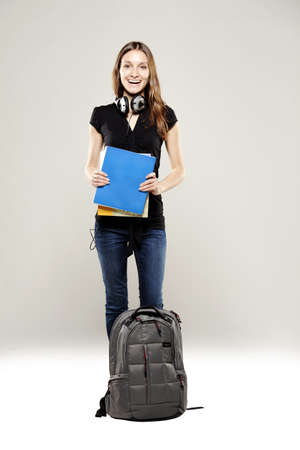 Beautiful young student with school bag and books photo