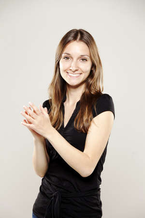 Beautiful young woman clapping and smiling for camera photo